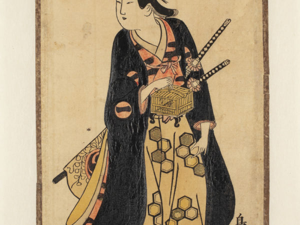 A Japanese print of an actor standing, wearing traditional robes. He has two staffs in his belt and holds a bamboo box.