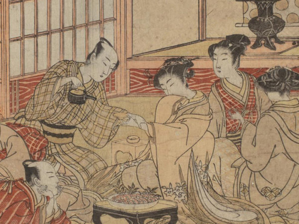 Japanese print of a group of people dressed in traditional clothes seated around a table. One man is reclining, another man holds a woman's hand whilst pouring tea, two other women look on.