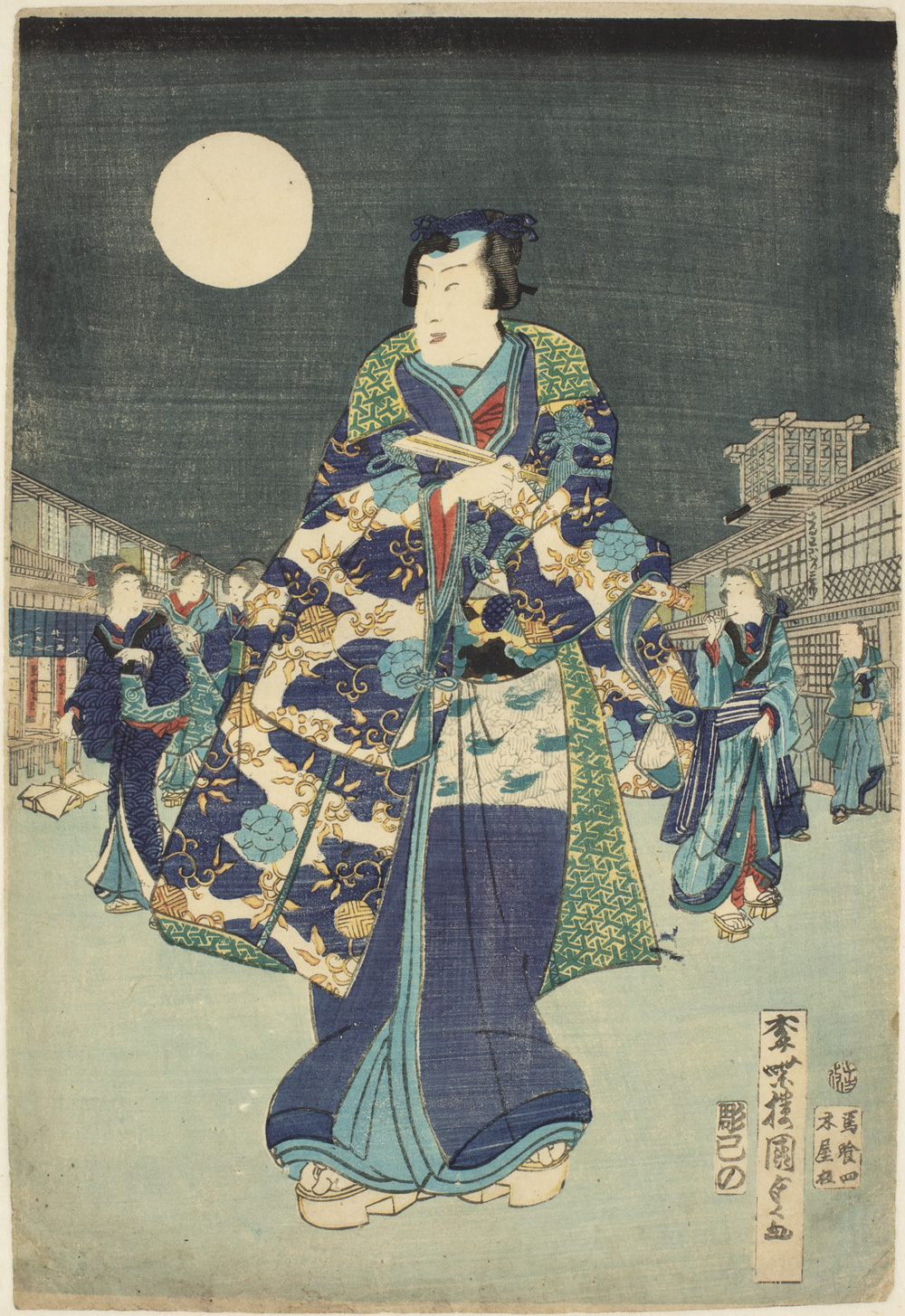 A Japanese print of a street scene at night, a full moon is in the sky. In the foreground there is a man dressed in colourful traditional clothes, other figures in similar clothes walk behind him, the buildings either side of the street recede.