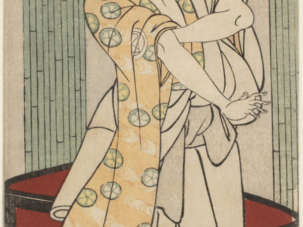 A Japanese print of an actor standing, looking to one side and one hand holding the sleeve of the traditional robes.