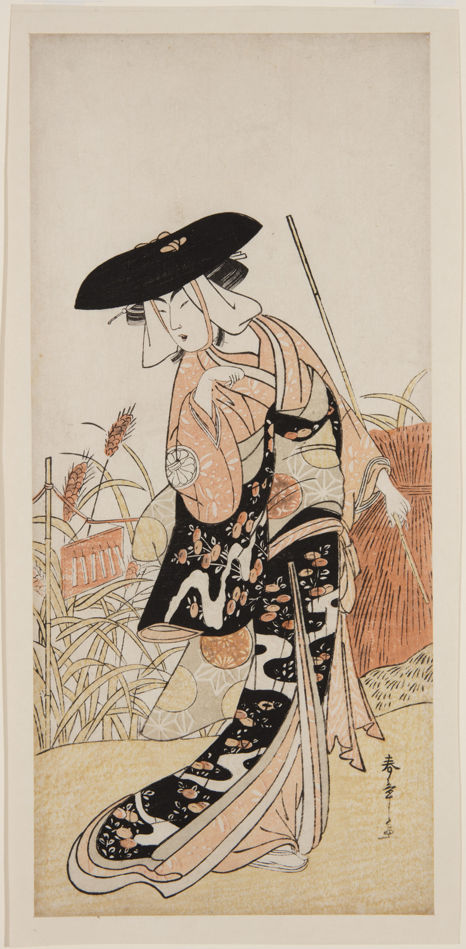 A Japanese print of an actor standing in a rural scene, looking down over the shoulder and wearing a large hat and long traditional robes.