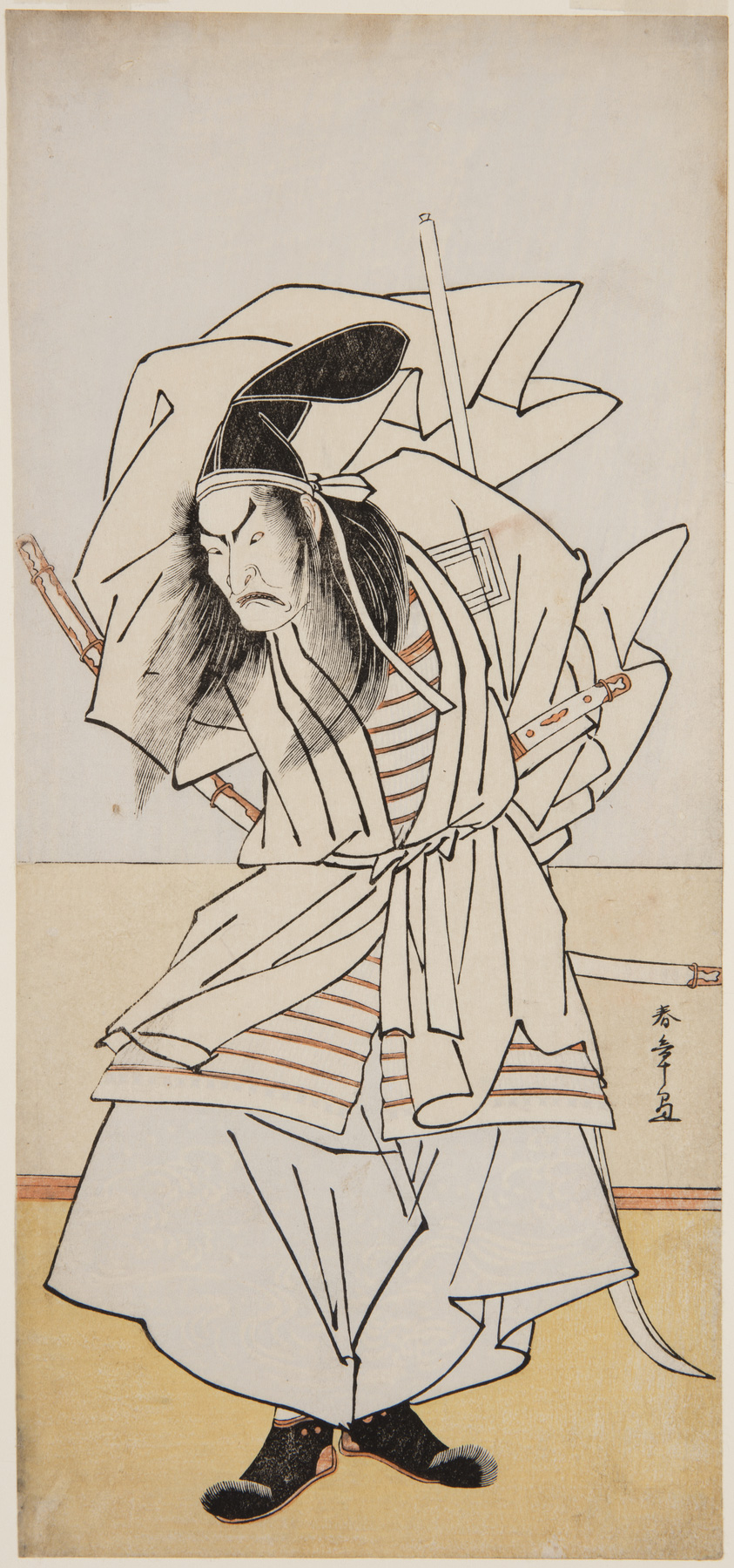 A Japanese print of an actor posed legs bent, looking down. He is wearing samurai traditional robes with his swords and staff in the back of his belt.