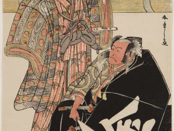 A Japanese print of two actors dressed in traditional robes. One is seated and is draped in a black cloak, holding a fan, two swords are visible. The other stands behind him and is holding a dish.