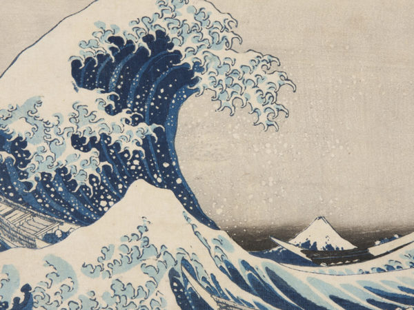Japanese print of a dramatic wave, a fishing boat and fishermen are engulfed by the wave, Mount Fuji can be seen in the background.