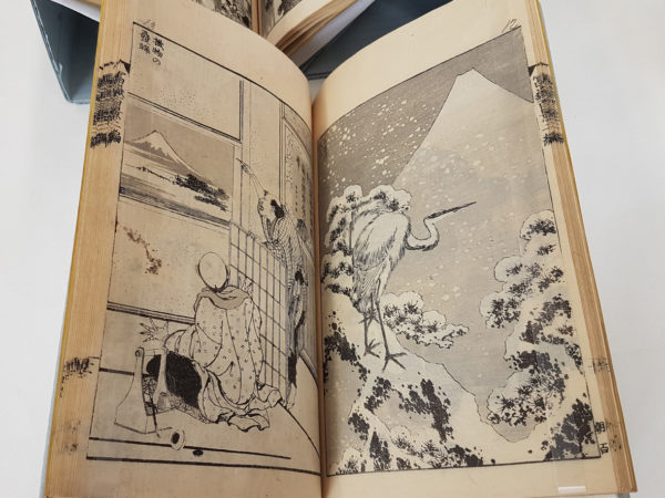 Image of an open Japanese book showing two pictures. One of two figures dressed in traditional costume looking out of a window at Mount Fuji. the other of a standing stork in a snowy landscape with Mount Fuji behind.