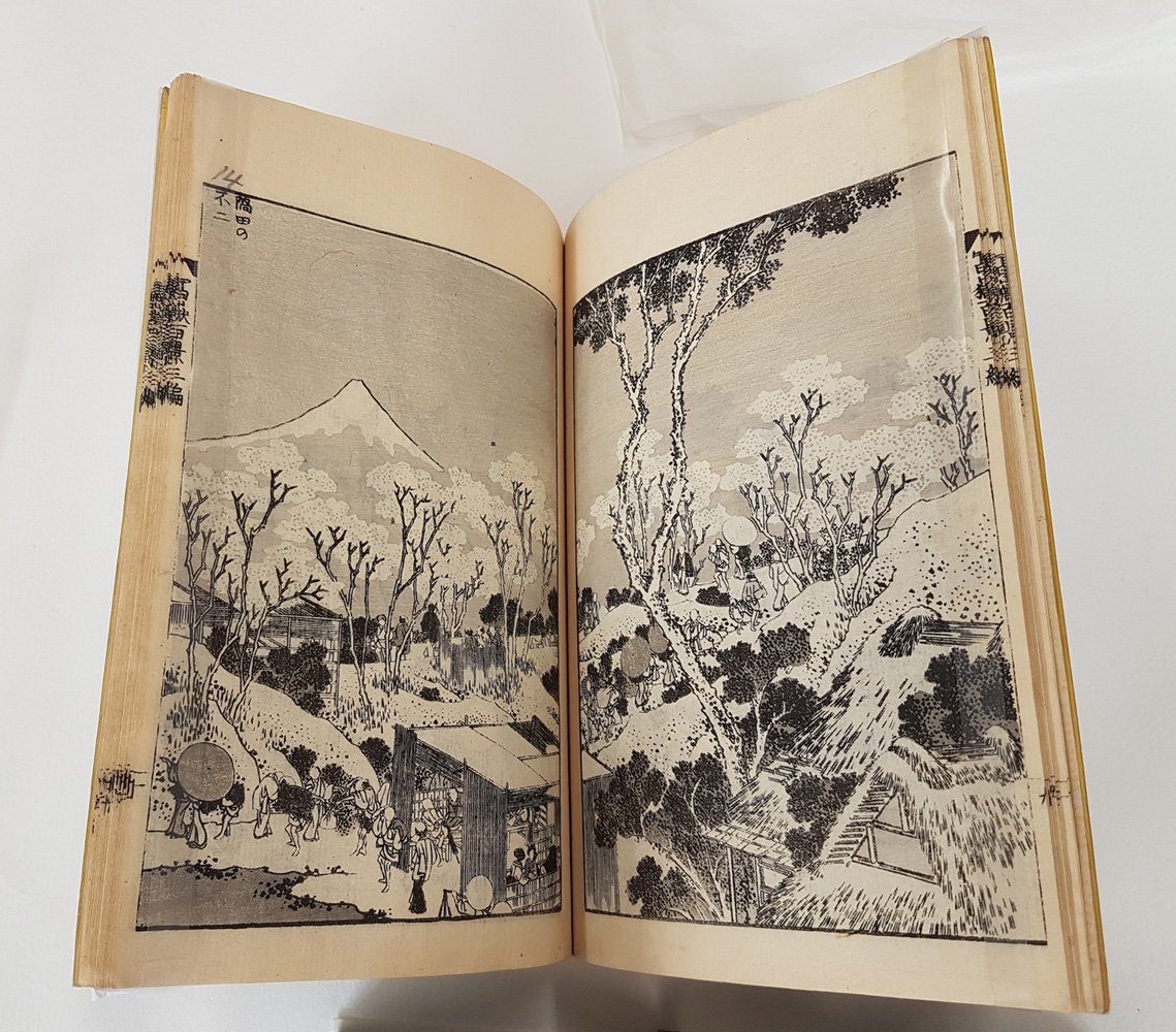 Image of open pages of a Japanese book showing a landscape, in the foreground is a building with people passing by, dressed in traditional clothes walking along the road that leads over the hills, through the trees, in the background is Mount Fuji.