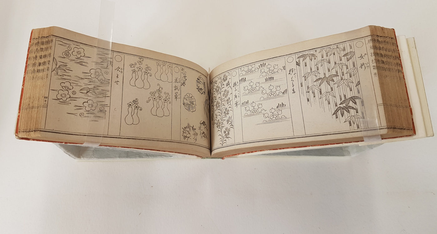 Image of the pages of an open Japanese book showing a series of six motifs including flowers and bamboo shoots.