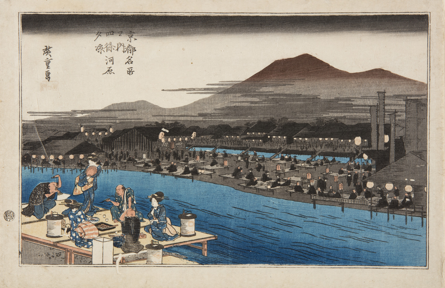 Japanese print of a landscape, in the foreground a group of two men and three women (geisha), dressed in traditional clothes, sit on a platform eating by the river bank, one woman stands and holds a fan to her face. On the other side of the river there are lots of other platforms and people, mountains rise up behind.
