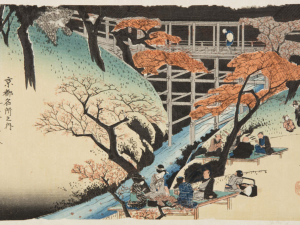 Japanese print of a landscape, people dressed in traditional clothes sit on platforms under maple trees by a river bank, behind is a wooden bridge and a figure looks down at the view.