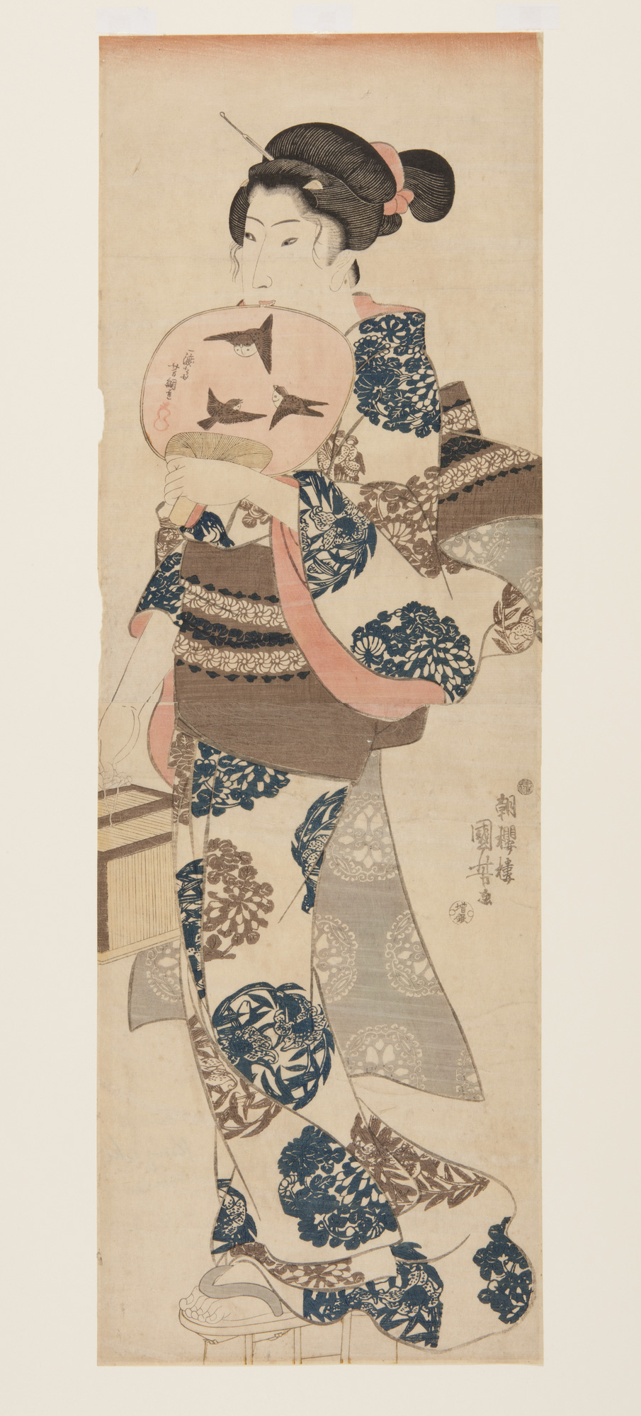 Japanese print of a woman dressed in traditional clothes, bird motifs on the fan she holds to her face and plant motifs on her kimono.