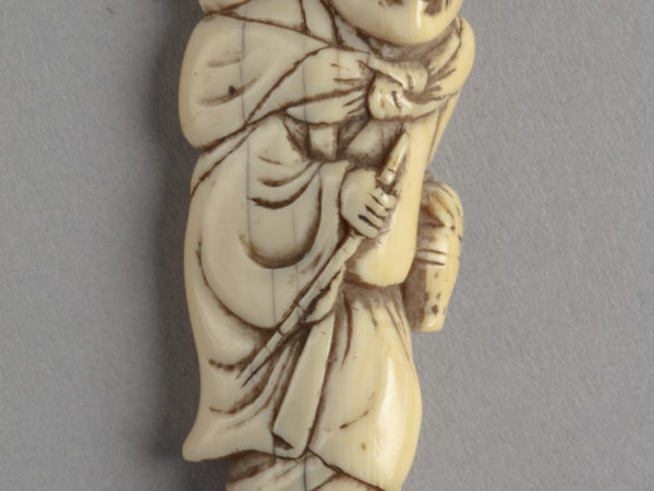 A Japanese ivory netsuke of a standing man holding a stick and alms basket with a small monkey on his shoulder.