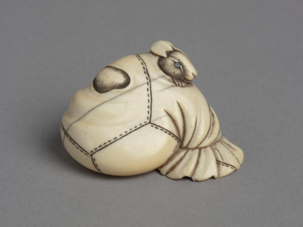 A Japanese ivory netsuke of a rat poking its head through a hole in a stitched rice-bag.