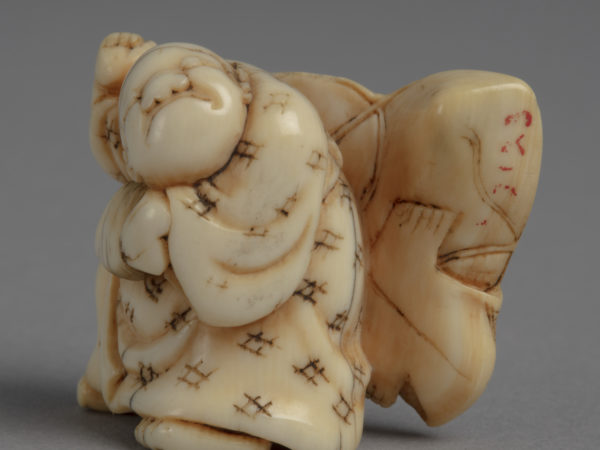 A Japanese ivory netsuke of a boy with a reel in his left hand and a kite over his back painted with a stern face.