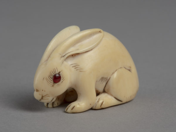 A Japanese ivory of a netsuke of a crouched white rabbit. Eyes are inlay with red coral.