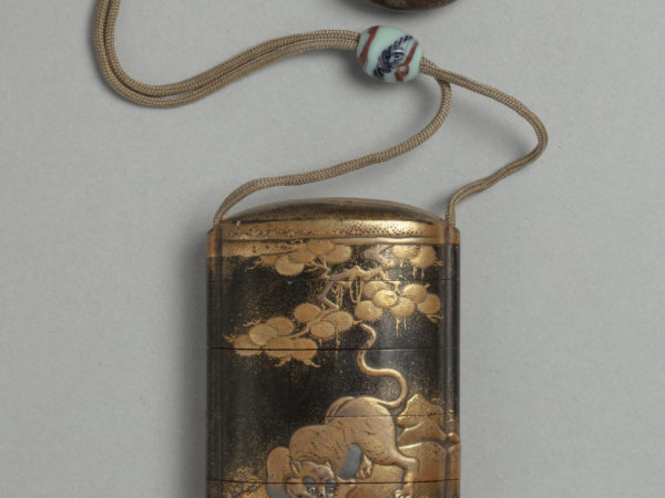 A Japanese black and gold lacquered five compartment inro box with dragon and tiger design, attached to a circular lacquer netsuke toggle.