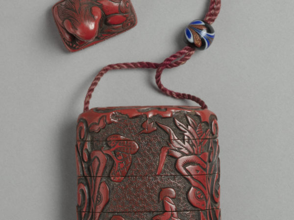 A Japanese red lacquer inro box with five compartments carved with a garden landscape, strung to a carved netsuke toggle in the form of a lion.