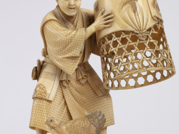 A Japanese carved ivory okimono ornament of a man with kimono, netsuke and tobacco pouch holding a chicken coop.