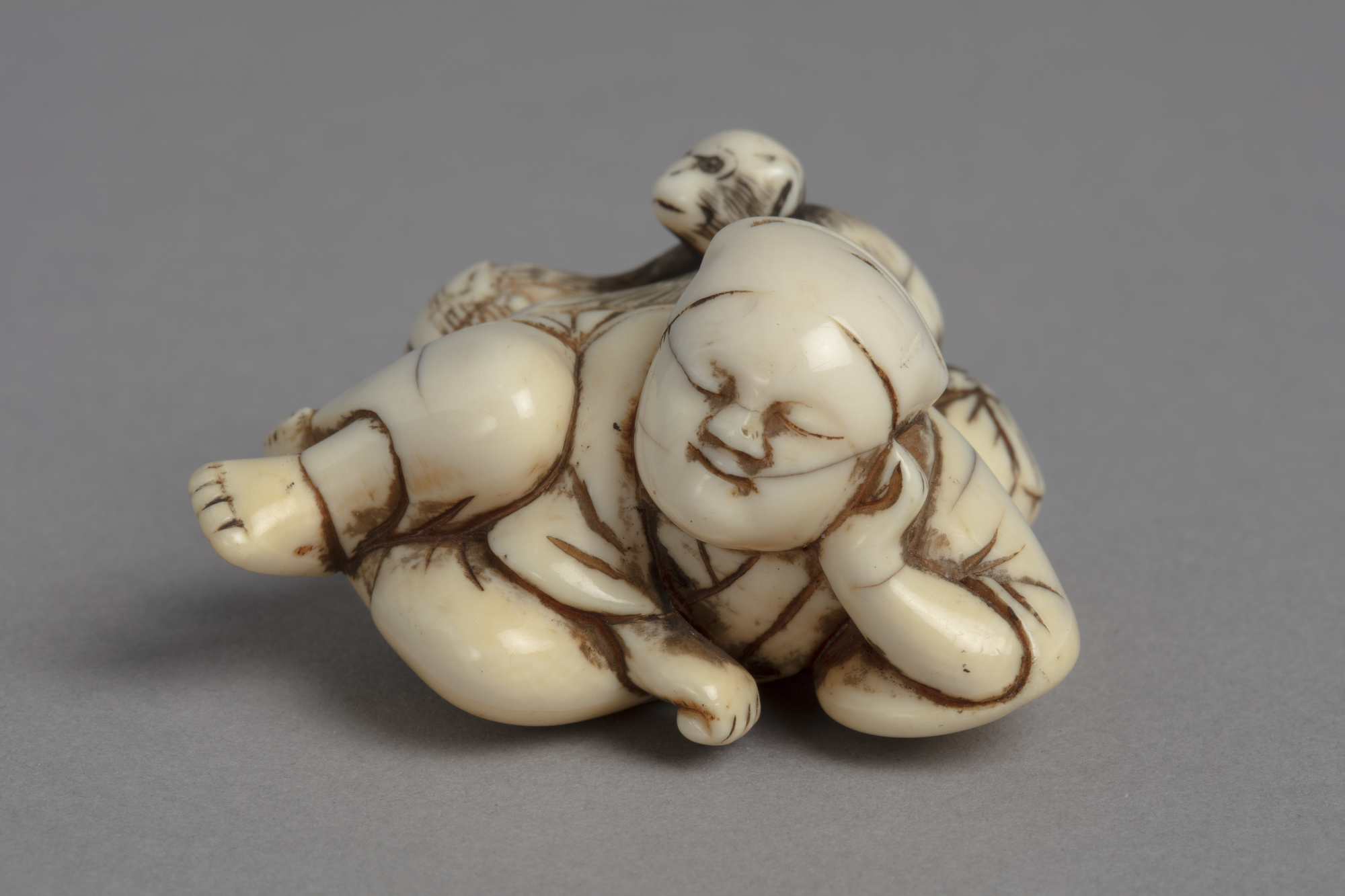 A Japanese ivory netsuke of a monkey stealing from a basket behind the back of a sleeping monkey trainer.