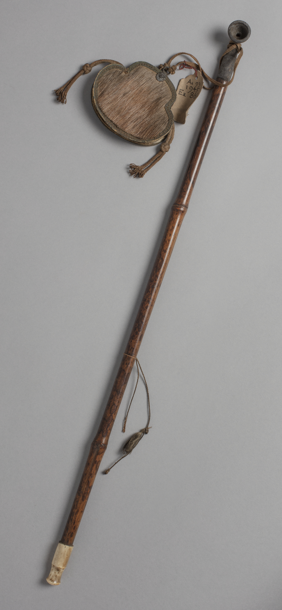 A Japanese tobacco pipe with small bowl attached to a tobacco pouch made of deer hide.