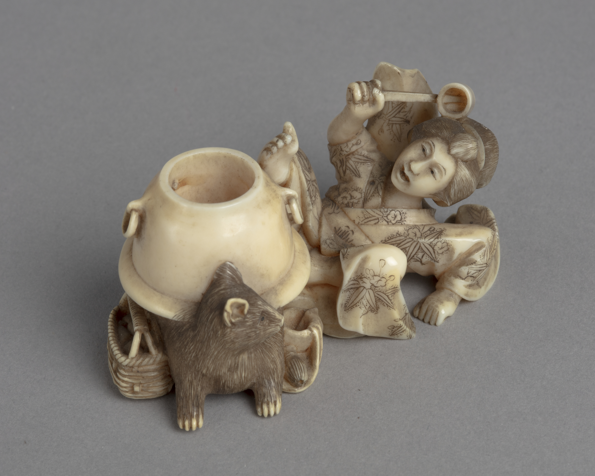 A Japanese ivory okimono ornament of a lady fallen on her back in alarm at the half-badger half-kettle before her.