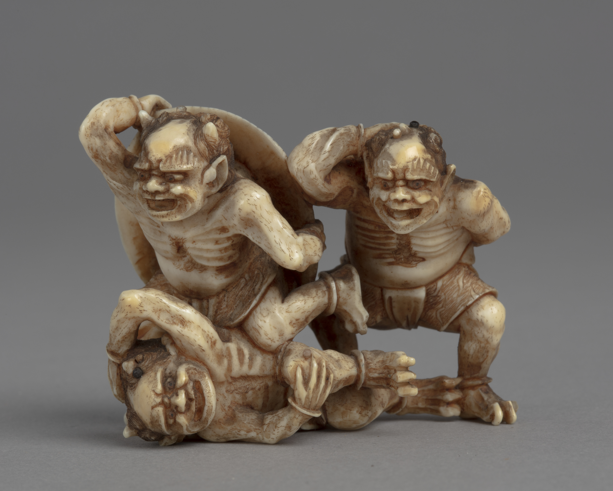 A Japanese ivory okimono ornament with three demons cowering and running away from the soybeans being thrown at them.