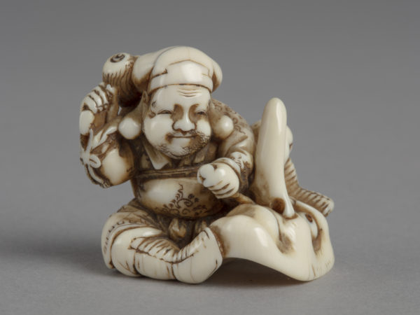 A Japanese ivory netsuke of Daikoku chiselling out the nostril of a long-nosed mask using his magic mallet.
