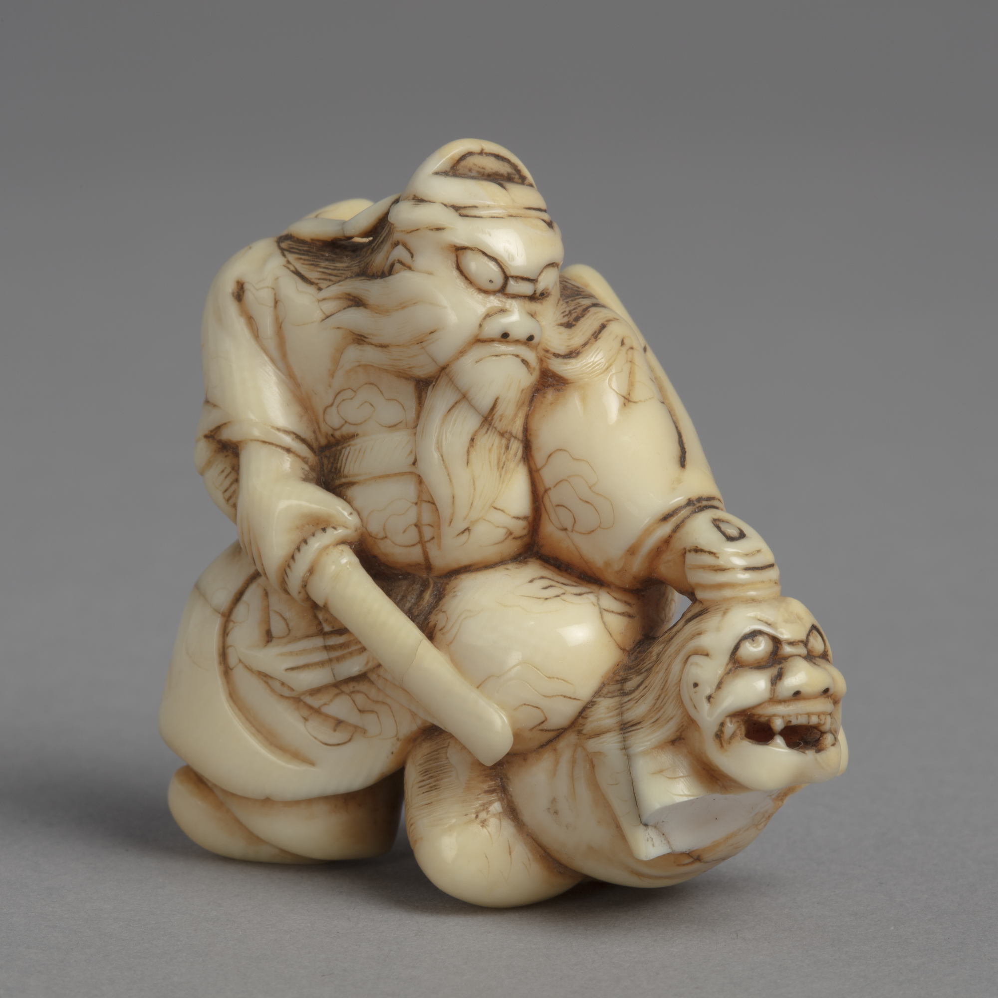 A Japanese ivory netsuke of Shoki kneeling on a demon, grasping it by the hair and pointing a sword at it.