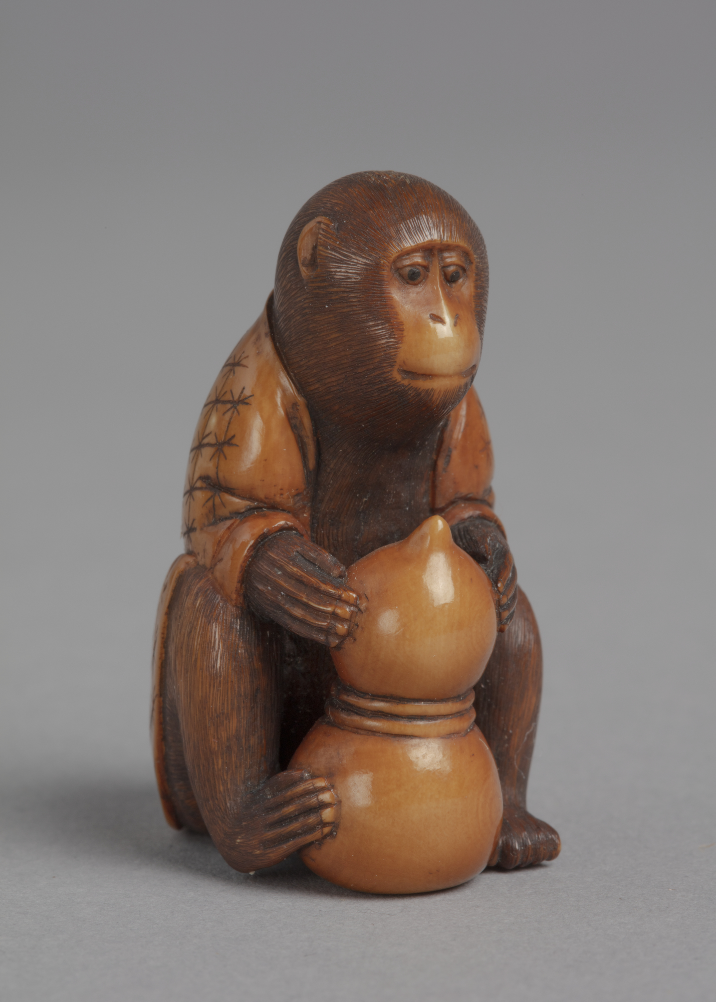A Japanese boxwood netsuke of a monkey wearing a robe, seated and holding a double gourd in its paws.