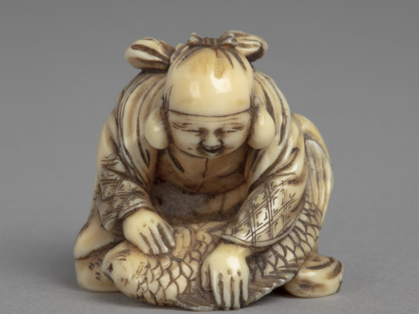 A Japanese ivory netsuke of Ebisu, one of the Seven Lucky Gods, kneeling over a large sea bream.