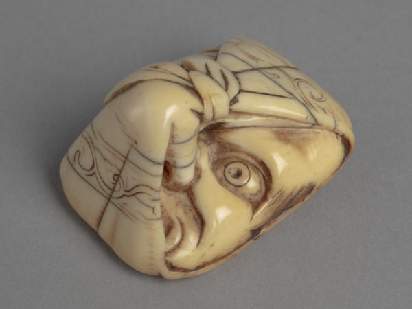 A Japanese ivory netsuke of a Tengu mask of a face with elongated nose wrapped in cloth. Only the left eye and nose is seen.