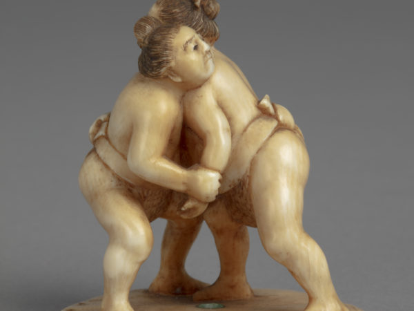 A Japanese ivory okimono ornament of two sumo wrestlers locked in a match.