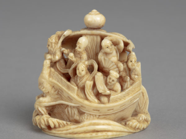 A Japanese ivory okimono ornament of the Seven lucky Gods aboard the Ship of Good Fortune which has the head of a dragon.