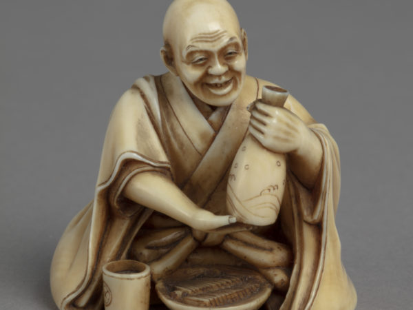 A Japanese okimono ornament of a seated man holding aloft a sake flask, a bowl of noodles and cup before him.