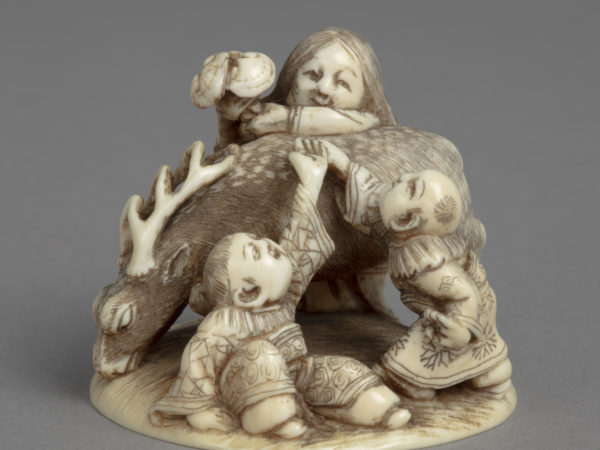 A Japanese ivory okimono ornament of a woman passing the Fungus of Immortality over a deer to two boys in Chinese dress.