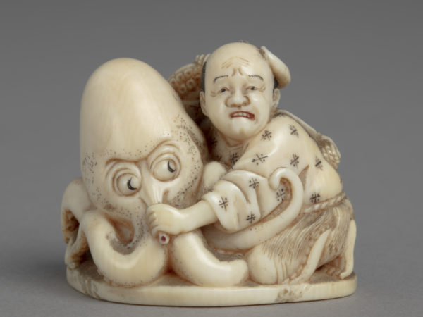 A Japanese ivory okimono ornament of a fisherman wrestling an octopus and pulling its nose.