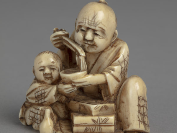 A Japanese ivory okimono ornament of a seated man eating noodles beside a small boy.