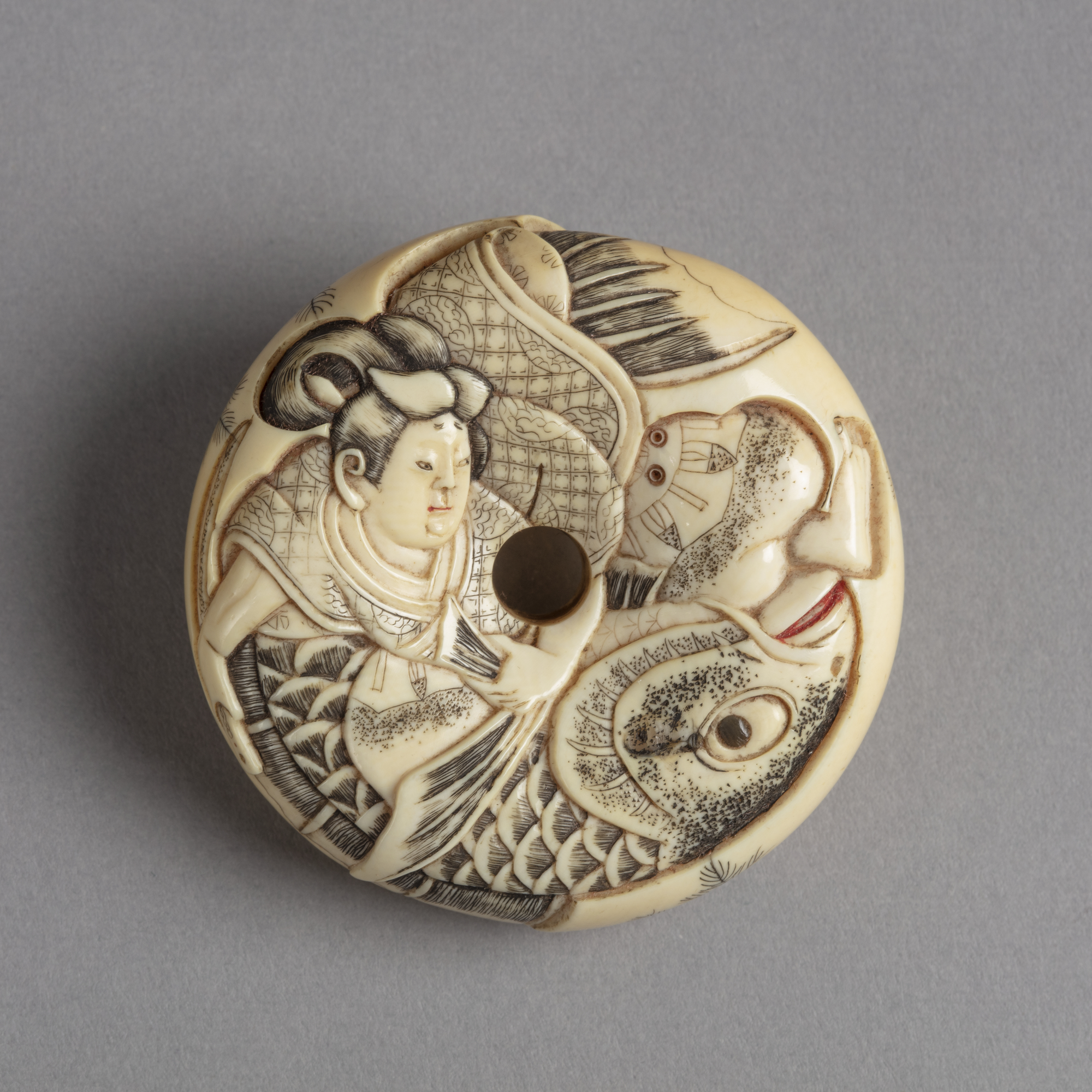 A Japanese ivory netsuke of a man fighting a very large fish carved on a doughnut-shaped disk.