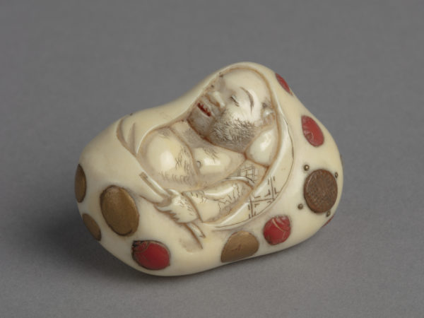 A Japanese ivory netsuke inlay with abalone, red coral, wood and gold paint, of Hotei asleep in his treasure bag.