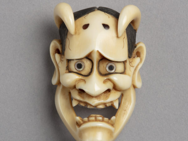A Japanese ivory mask netsuke of Hannya the face of a jealous woman who took on the features of a demon including its horns.