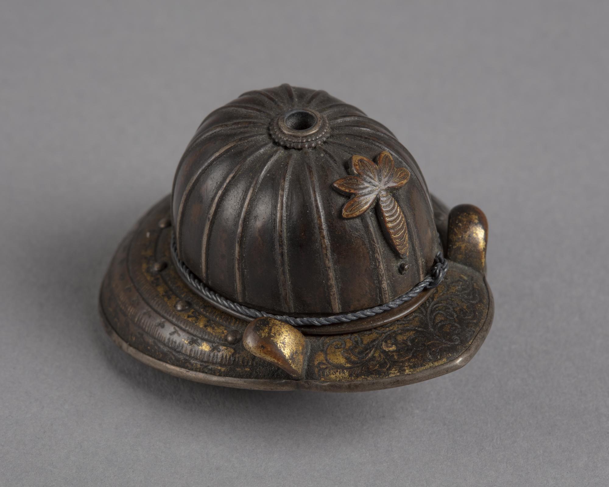 A Japanese metal netsuke of a Kabuto, a metal helmet worn by samurai soldiers.
