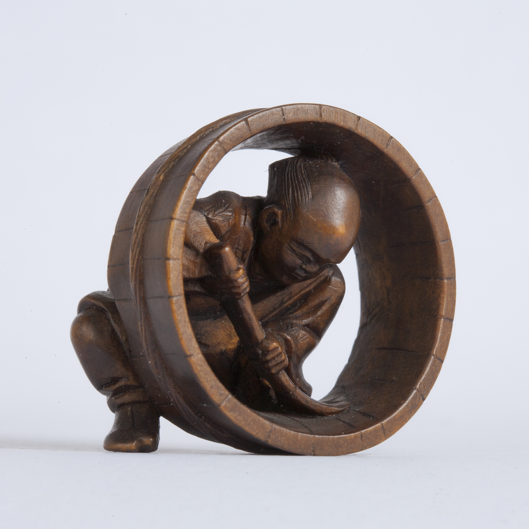A Japanese boxwood netsuke of a cooper making the body of a large wooden barrel.