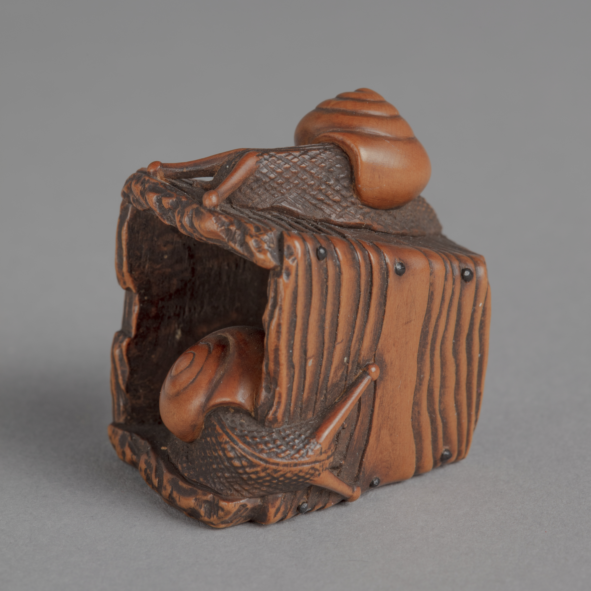 A Japanese boxwood netsuke of a pyriform wooden well bucket with one snail on top and one snail inside.