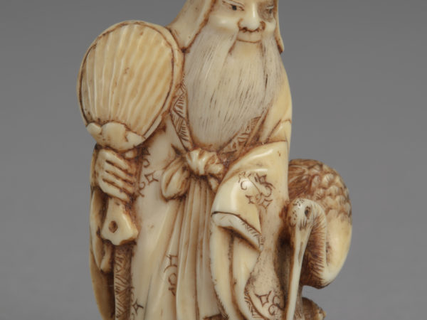 A Japanese ivory netsuke of Fukurokuju a god of wisdom. He stands holds a fan in his right hand, a stork by his left side.
