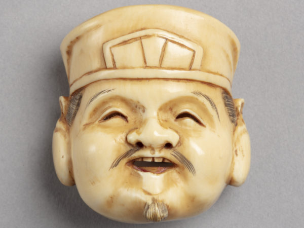 A Japanese ivory netsuke of the smiling face of Ebisu. He wears a hat and has a fine moustache and small beard.