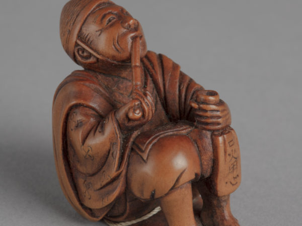 A Japanese boxwood netsuke of a seated man looking up and smoking a long pipe, left hand on left knee and holding a bag.