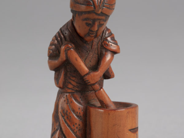 A Japanese boxwood netsuke of a standing woman with movable head washing clothes in a cylindrical tub with a pestle.