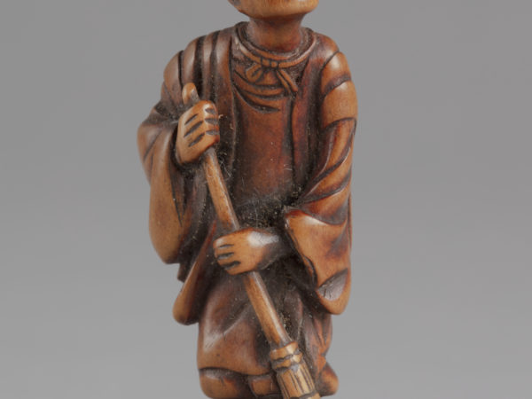 A Japanese boxwood netsuke of a robed elder with a broom sweeping the ground.