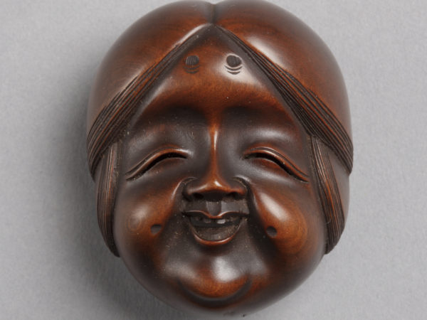 A Japanese boxwood netsuke of the face of Okame, the goddess of mirth. She has large cheeks and a joyful smile.