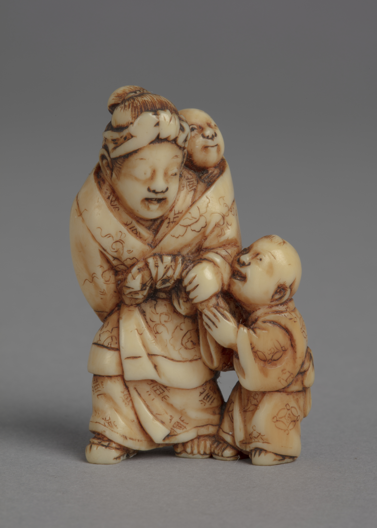 Japanese ivory netsuke of a standing mother in kimono and headscarf with a baby bundled on back and a boy to her left.