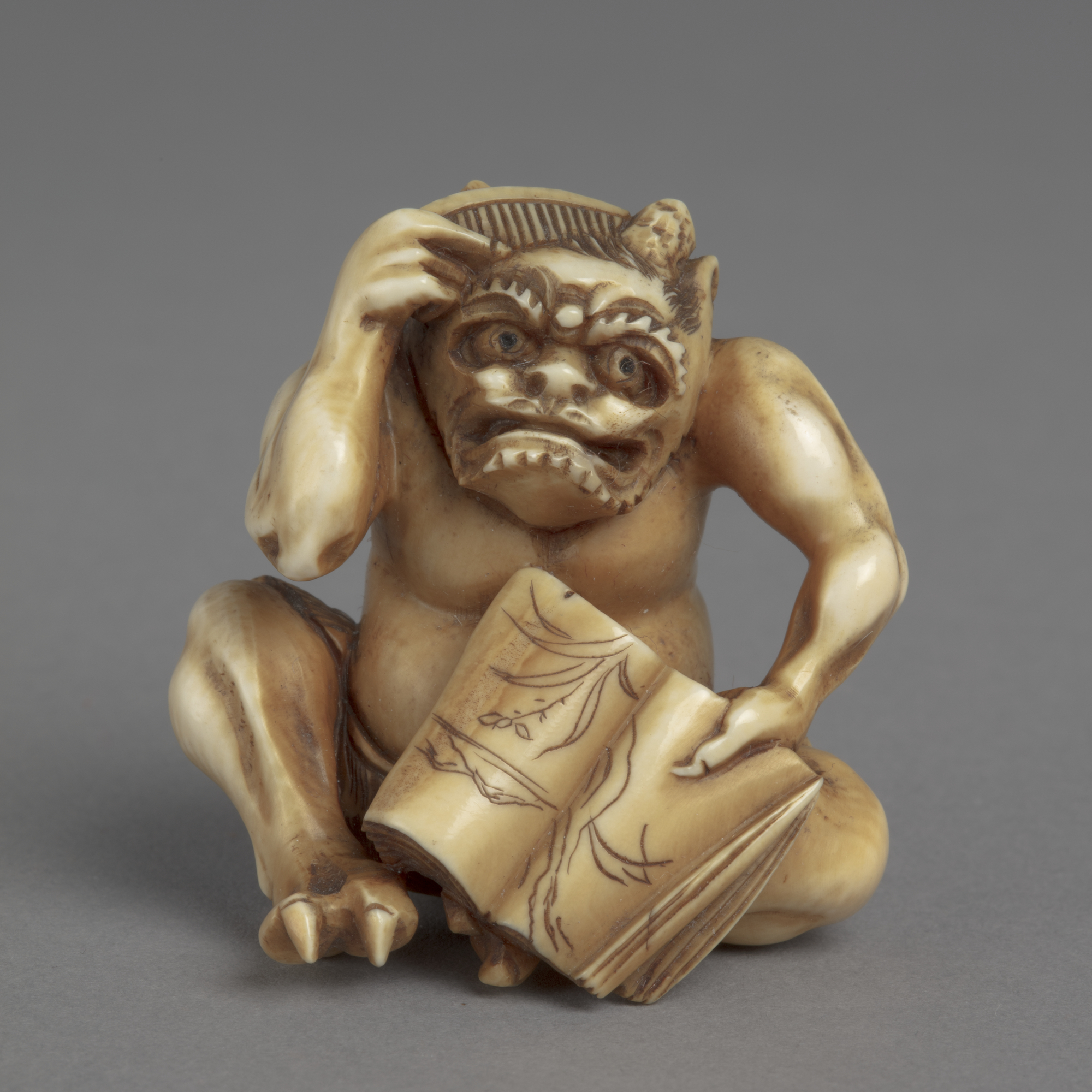 A Japanese ivory okimono ornament of a seated demon holding open book and combing long hair with left hand.